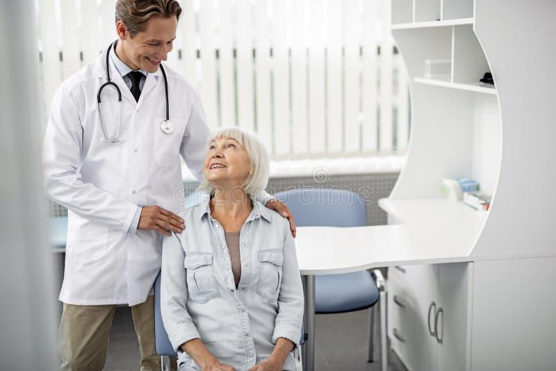 年长夫人坐站立在她旁边的主席和医生 免版税库存图片