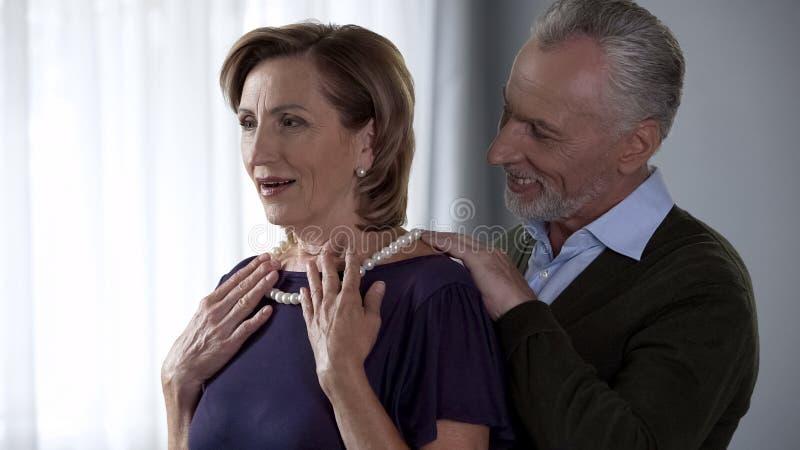 年长夫人对新的珍珠项链高兴,从丈夫庆祝出席 免版税库存照片