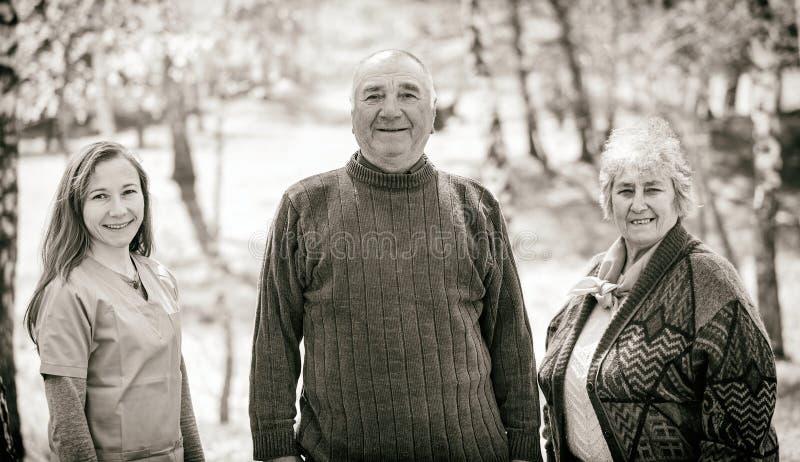年长夫妇和年轻照料者 免版税库存图片