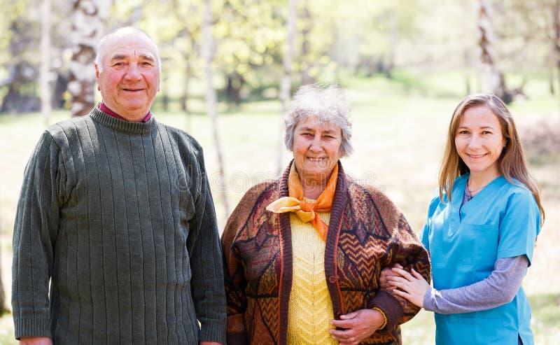 年长夫妇和年轻照料者 免版税图库摄影