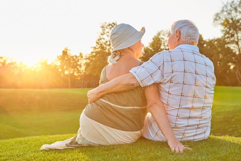 年长夫妇坐草 免版税图库摄影