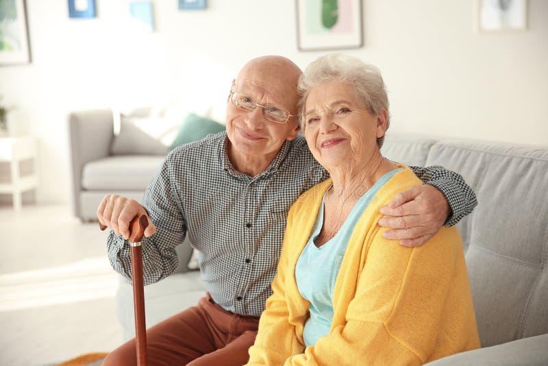 年长夫妇坐长沙发 免版税库存图片