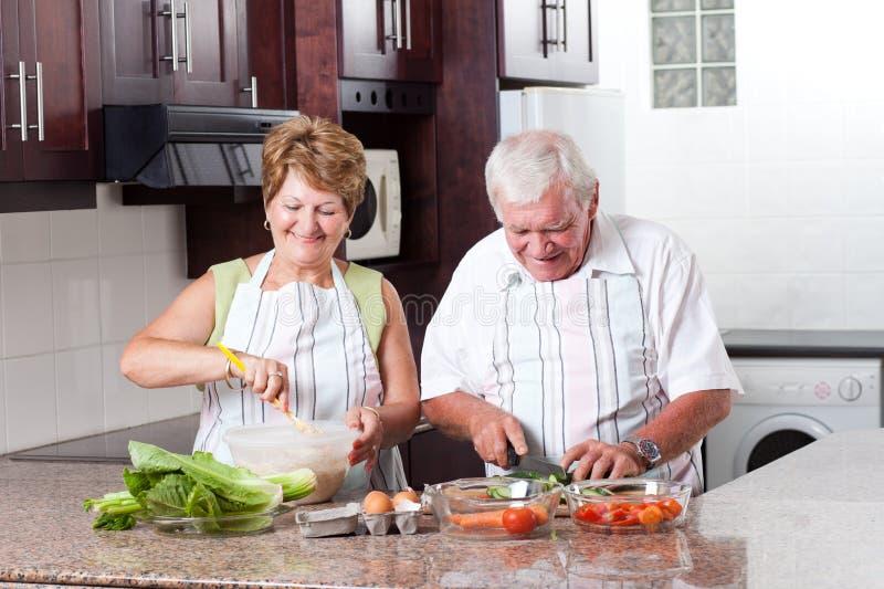 年长夫妇烹调 免版税库存图片