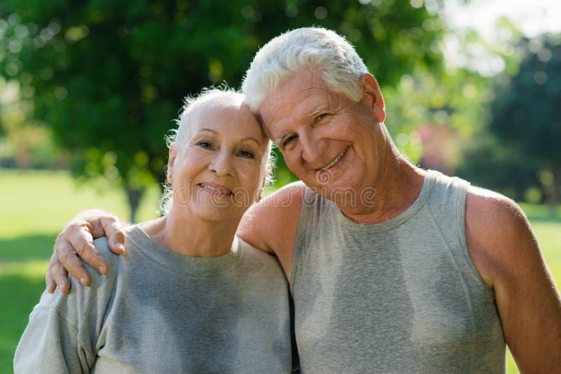 年长夫妇纵向在健身以后的在公园 库存图片