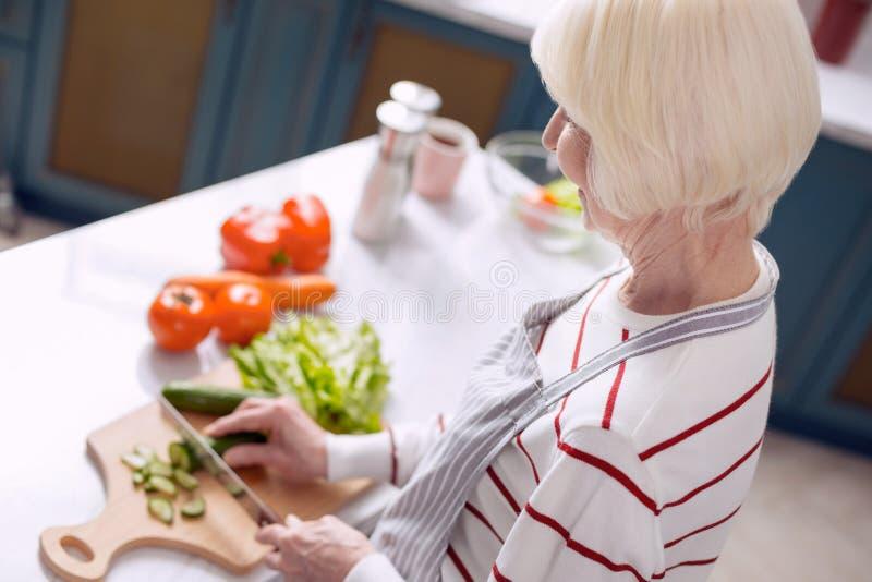 年长妇女切口黄瓜在厨房里 库存照片