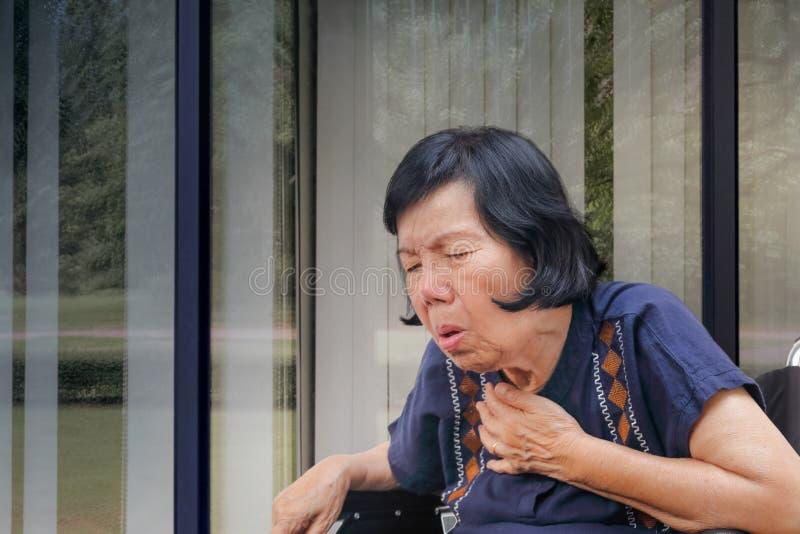 年长妇女咳嗽,阻气 免版税库存照片