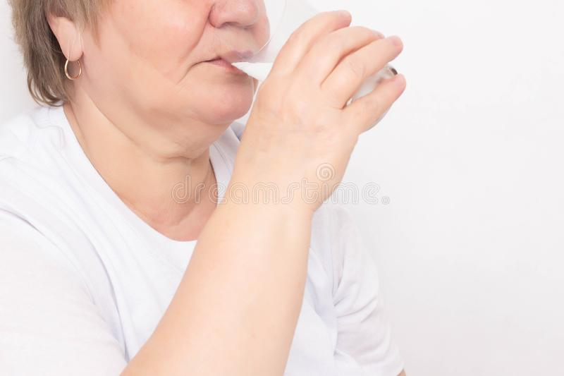 年长妇女喝从一块玻璃的水在白色背景,体液,失水损失的概念在老人的 免版税库存图片