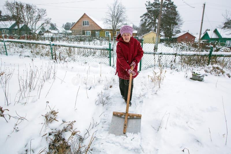 年长妇女在他的农村房子附近清洗雪 帮助 图库摄影