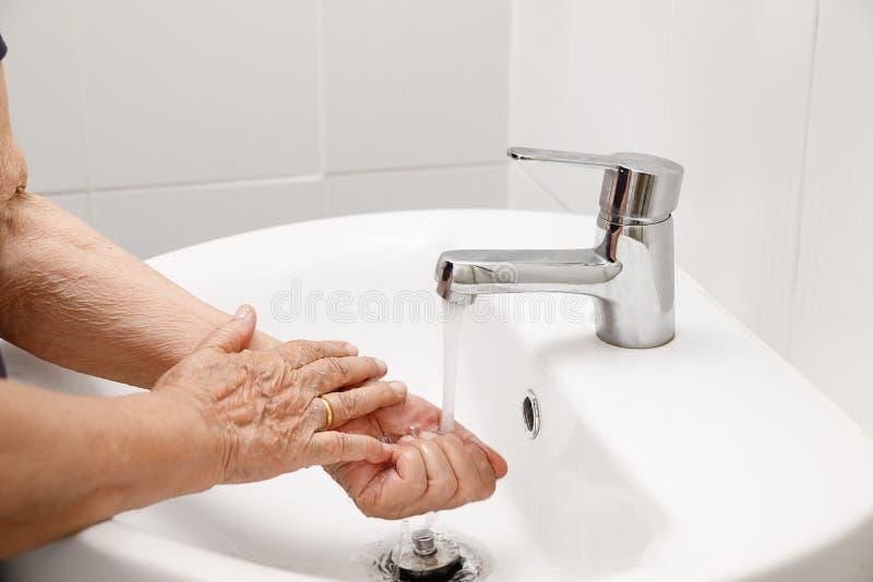 年长妇女在卫生间里洗手 免版税库存照片