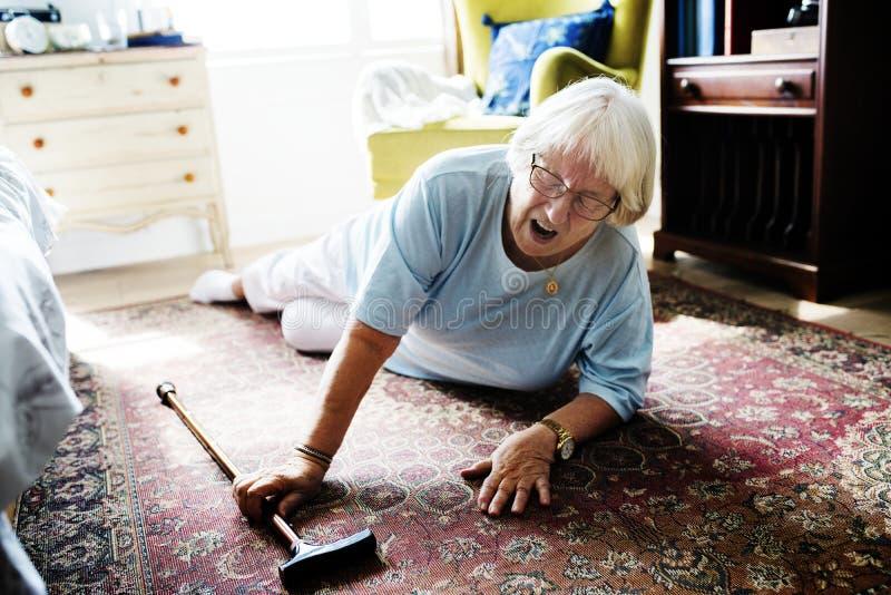年长妇女在地板上跌倒了 免版税库存图片