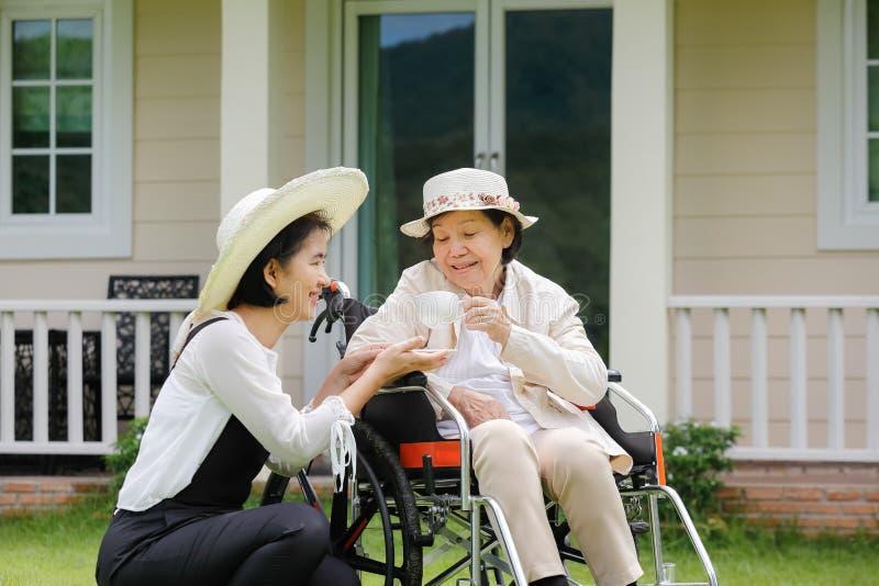 年长妇女在有女儿的后院放松 免版税库存图片