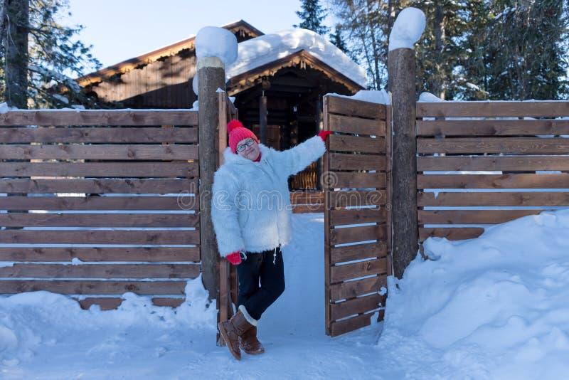 年长妇女在门附近站立在随风飘飞的雪中的一个木房子附近在森林里 库存图片