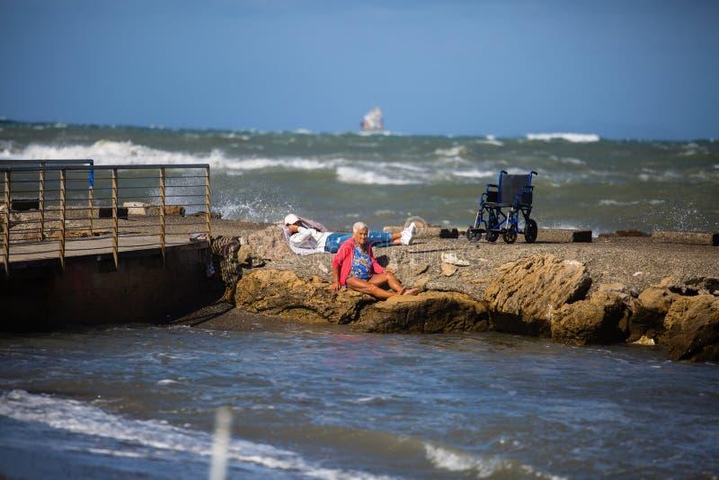 年长妇女坐岩石和她的轮椅在散步的海岸线附近:三角浪在大风天 免版税图库摄影