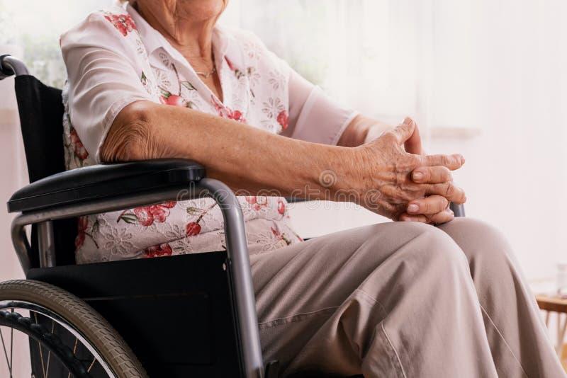 年长妇女坐轮椅在老人院 免版税库存照片