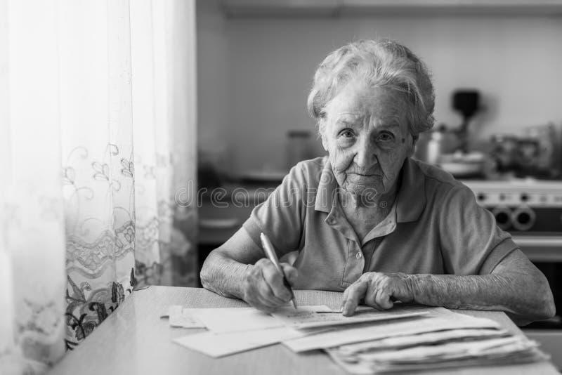 年长妇女填好坐在厨房里的电费单 免版税图库摄影