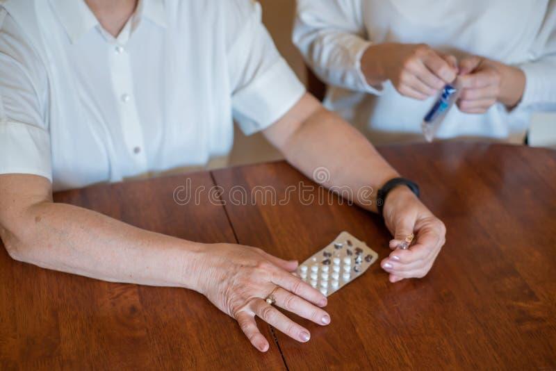 年长妇女拿着药片和细颈瓶 领抚恤金者的手特写镜头有药物的 年轻女人打开注射器 女儿是 免版税库存图片