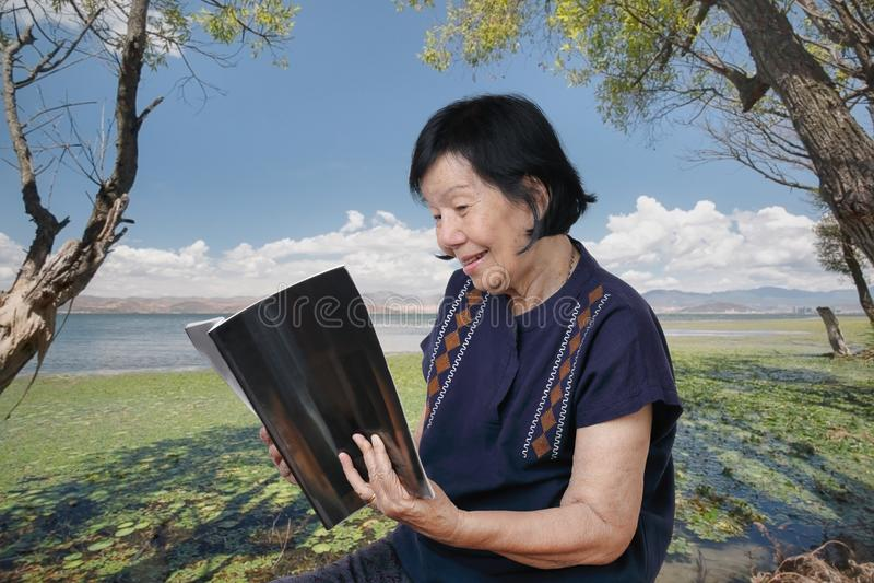 年长妇女松弛读书一本杂志在后院 免版税库存照片