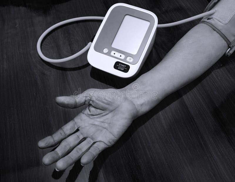 年长妇女检查血压 并且与数字压力测量的心率 黑白口气 愉快变老和医疗 免版税库存照片