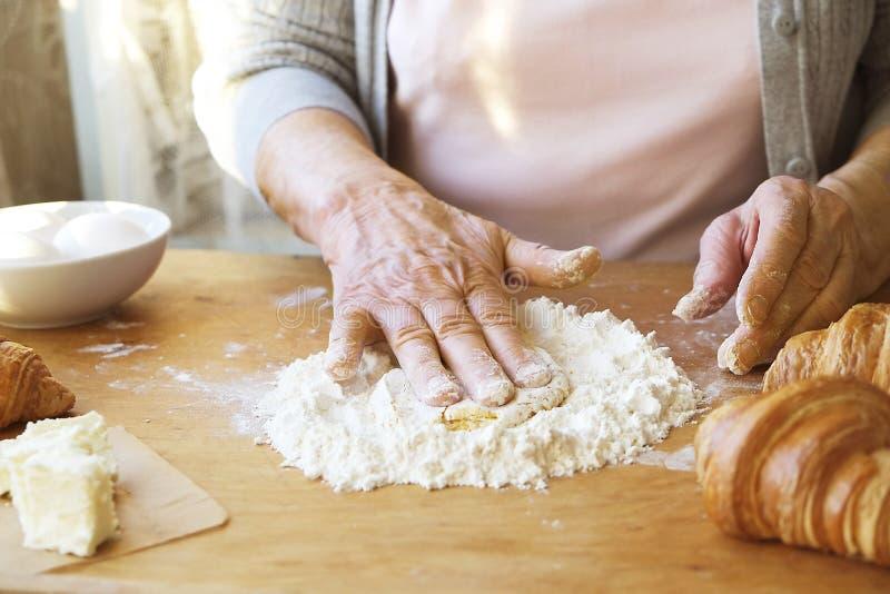 年长妇女烹调法国新月形面包,露出起皱纹的手,成份,软的温暖的早晨光,顶视图 免版税库存照片
