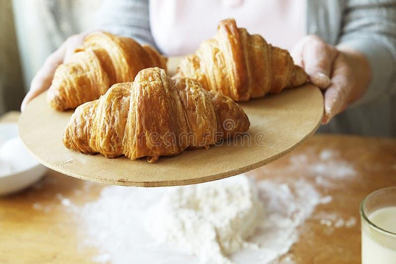 年长妇女烹调法国新月形面包,露出起皱纹的手,成份,软的温暖的早晨光,顶视图 图库摄影