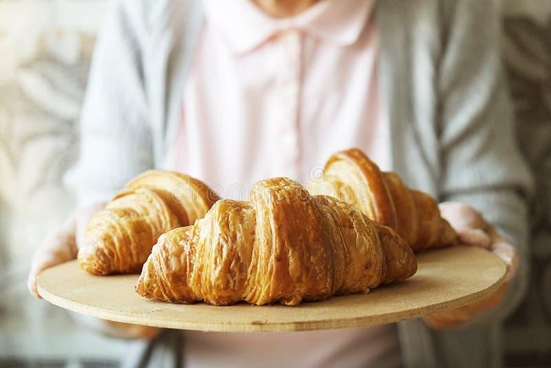 年长妇女烹调法国新月形面包,露出起皱纹的手,成份,软的温暖的早晨光,顶视图 库存图片