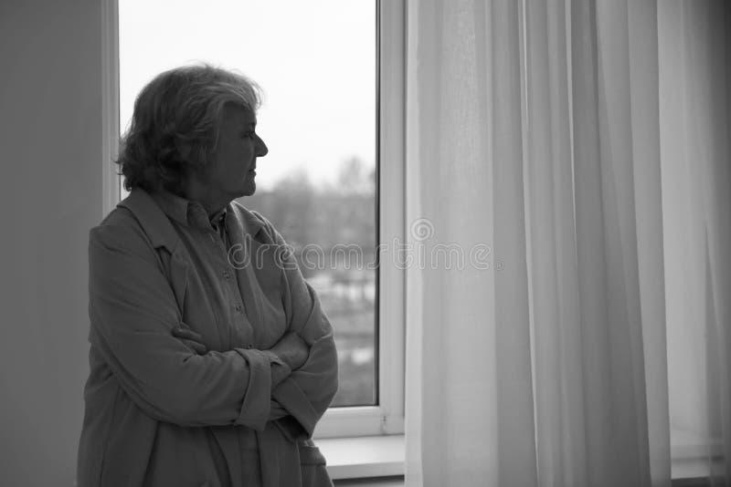 年长妇女画象在窗口,文本的空间附近的 黑白作用 免版税库存图片