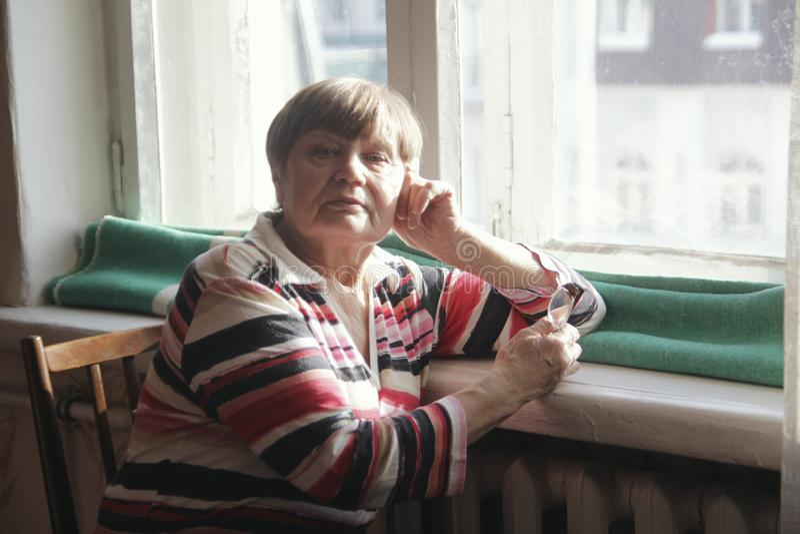 年长妇女画象戴眼镜的在家在窗口附近 库存图片