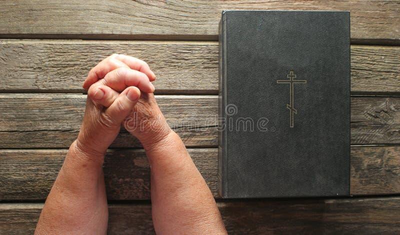 年长妇女的手在老土气委员会的圣经书附近祈祷 宗教概念,顶视图 库存图片