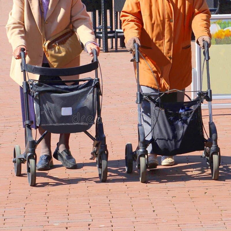 年长妇女街道步行者rollators购物 免版税库存图片
