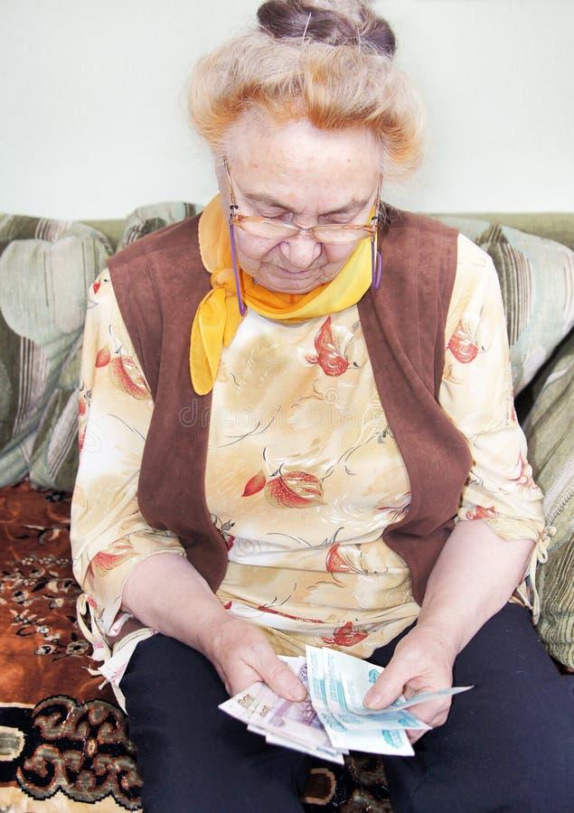 年长妇女计数货币 库存照片