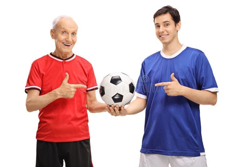 年长拿着橄榄球和poin的足球运动员和年轻球员 免版税图库摄影
