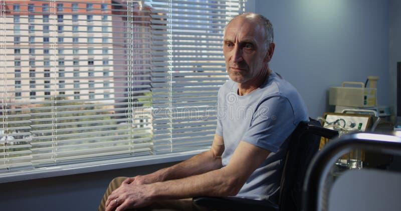年长男性患者在窗口附近的医院 库存照片