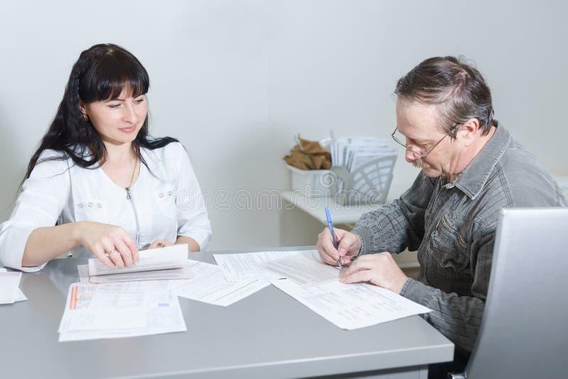 年长男性耐心标志在一位在知情同意的中年妇女医生文件的招待会对处理  免版税库存照片