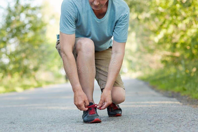年长男性运动员领带鞋带,作为播种的射击在跑步的锻炼以后休息,穿运动服,摆在室外 人runne 免版税图库摄影