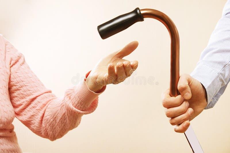 年长疗养所的成熟女性从医院人员护士得到帮助 关闭资深妇女的年迈的起皱纹的手 g 免版税库存照片