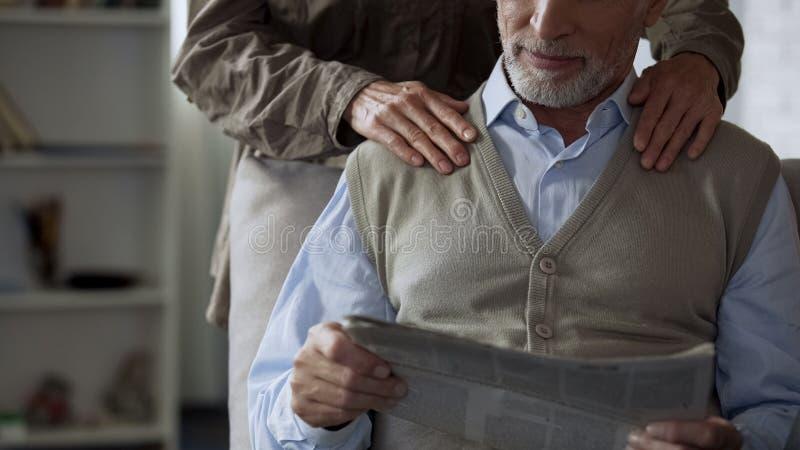 年长绅士读书报纸,拥抱从后面,爱恋的柔软的夫人 库存图片