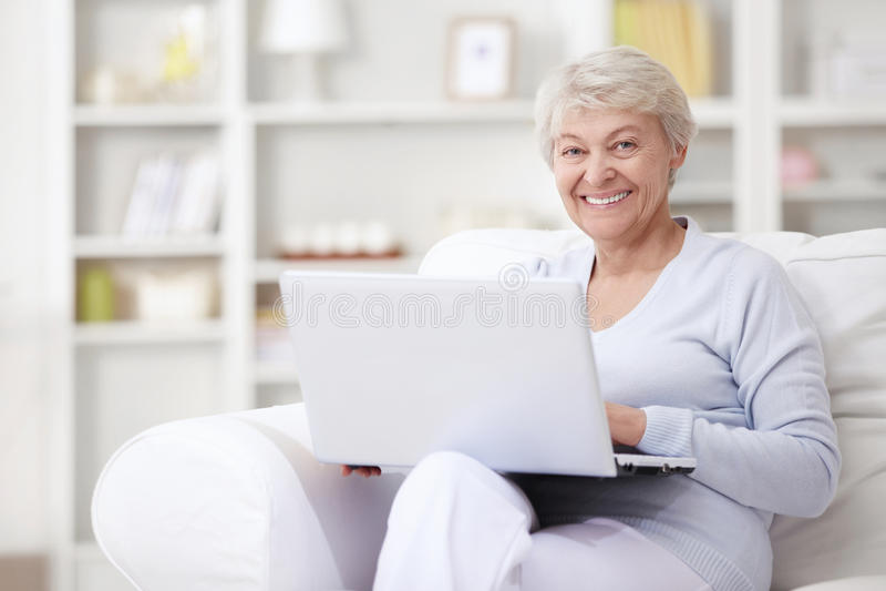 年长膝上型计算机妇女 库存照片