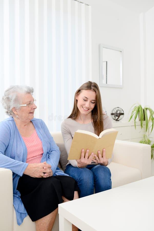 年长资深妇女的快乐的少妇阅读书在家 免版税图库摄影