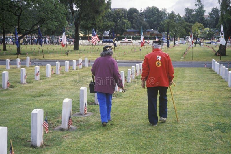 年长退伍军人和妻子在墓地 库存照片