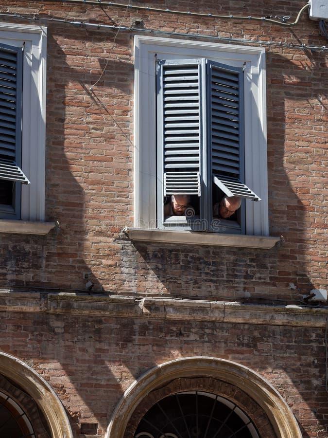 年长配偶从一个古老的宫殿的窗口观察 免版税库存图片