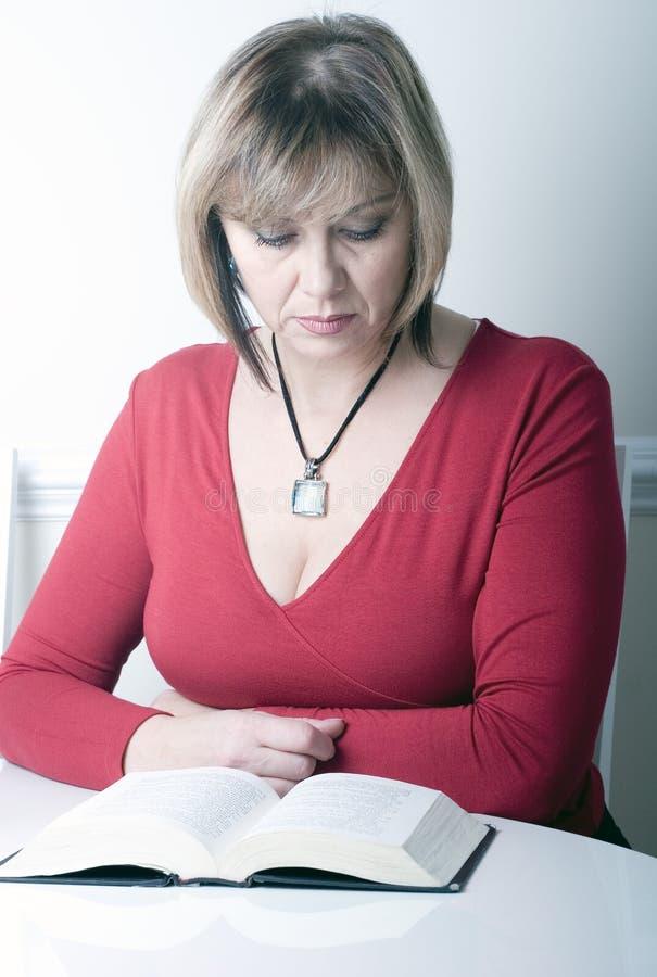 年龄可爱的美丽的中间读取妇女 免版税库存照片
