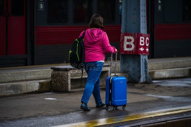 2019年,在罗马尼亚布加勒斯特的Gara de Nord Bucuresti火车北站站台上搬运行李的妇女 免版税图库摄影
