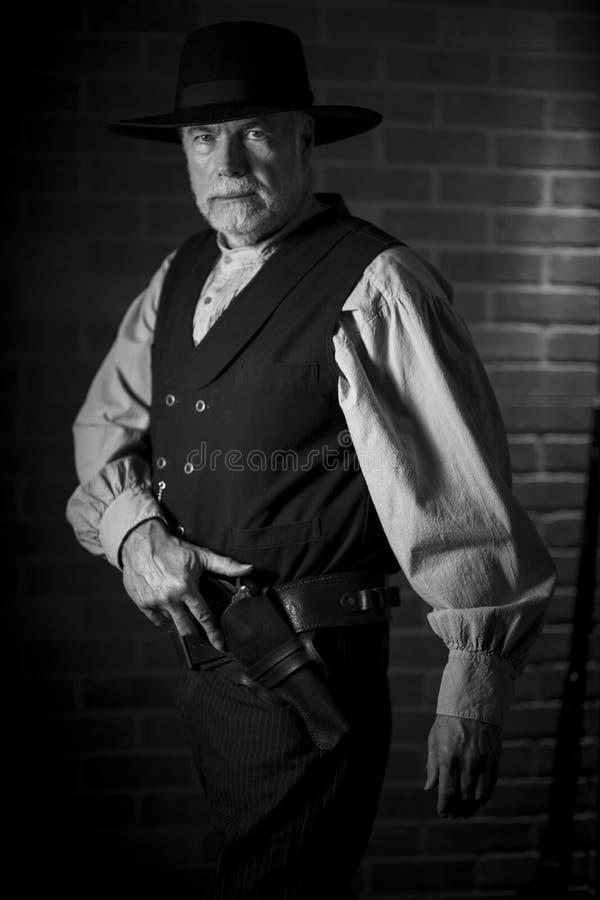 1885年,老西部牛仔准备用手枪对着相机 免版税库存照片