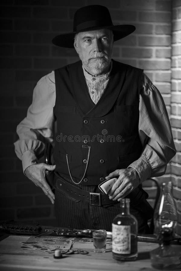 1885年,老西部牛仔站在酒吧里,准备拔枪 库存照片