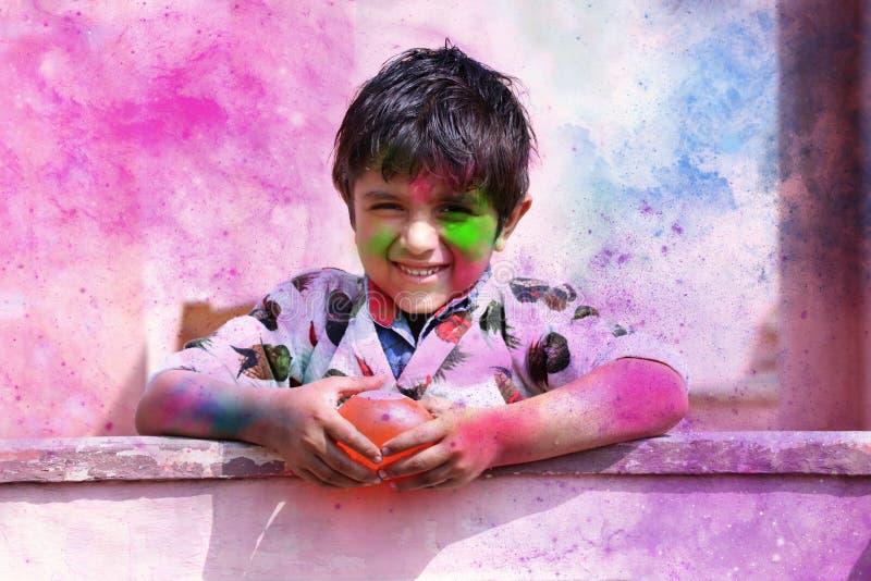 2019年3月,印度哈里亚纳邦的希萨尔,小男孩用颜色演奏 印度节的气球概念 免版税库存照片
