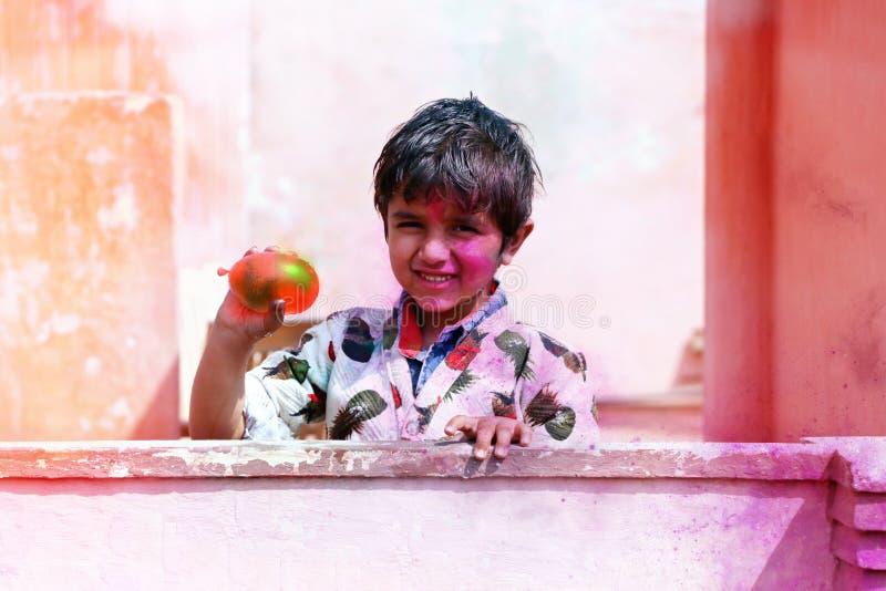 2019年3月,印度哈里亚纳邦的希萨尔,小男孩用颜色演奏 印度节的气球概念 免版税库存图片