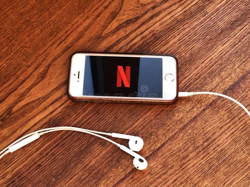 2019年12月,意大利帕尔马:Netflix公司标志图标在智能手机屏幕上用耳机在木桌上特写 Netflix可视化 库存图片