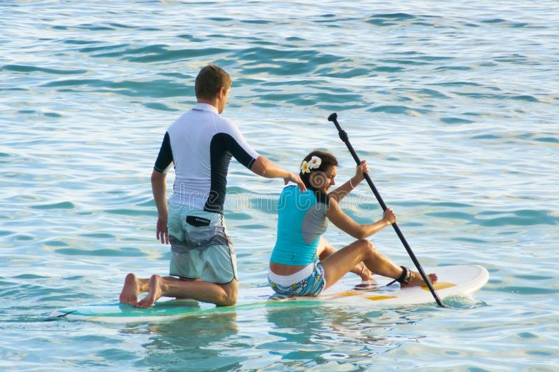 2012年6月-一对年轻夫妇冲浪太平洋waikiki海滩夏威夷美国 库存照片