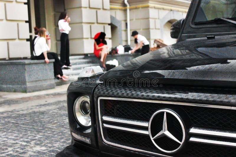 2011年5月21日,基辅-乌克兰 汽车的美好的房间 特写镜头正面图奔驰车以女孩为背景的G63 AMG 库存图片