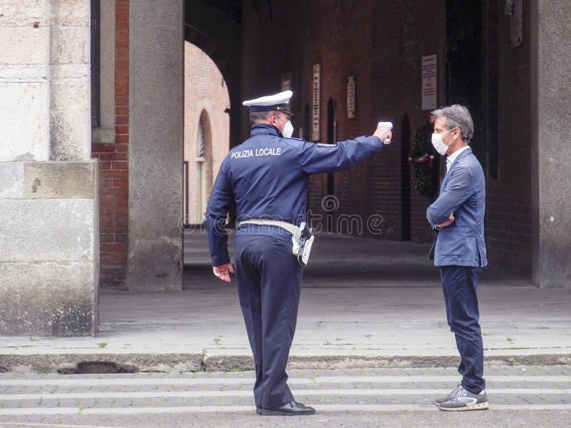 2020年5月13日,意大利伦巴第州克雷莫纳 — 当地警官,测量成年人 人体体温红外测温仪 免版税库存图片